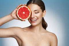 Smiling girl with grapefruit, natural organic raw fresh food concept Stock Photography