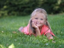 Smiling girl on grass. Little girl that is smiling and lies royalty free stock image