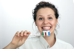Smiling girl with a green red blue toothbrush Royalty Free Stock Image