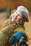 Smiling girl in grey beret. Smiling teenager blond girl sitting on a bench in autumn park Royalty Free Stock Photos