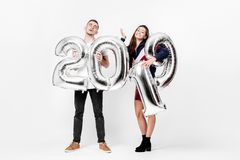 Smiling girl and guy dressed in a stylish clothes are having fun with balloons in the shape of numbers 2019 on a white stock photography