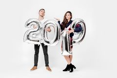 Smiling girl and guy dressed in a stylish clothes are having fun with balloons in the shape of numbers 2019 on a white stock photo