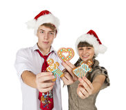 Smiling girl and the guy in red santa caps and gingerbread cooki Stock Image