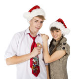 Smiling girl and the guy in red santa caps and gingerbread heart Stock Images