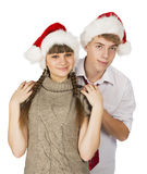 Smiling girl and the guy in red santa caps on a white isolated b Royalty Free Stock Image
