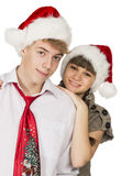 Smiling girl and the guy in red santa caps on a white isolated b Royalty Free Stock Photography