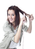 Smiling girl with hair iron (vertical) Royalty Free Stock Photos
