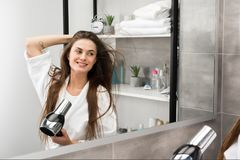 Smiling girl with hairdryer Stock Photos