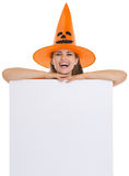 Smiling girl in Halloween hat with blank billboard Stock Photos