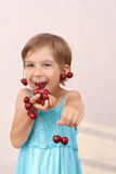 Smiling girl with handful of cherries. Smiling little girl with handful of cherries stock photography