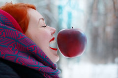 Smiling girl and hanging in air big red apple Royalty Free Stock Image