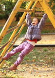 Smiling girl hanging on climbing frame Stock Photos