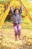 Smiling girl hanging on climbing frame Royalty Free Stock Image