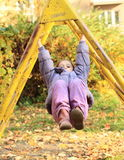 Smiling girl hanging on climbing frame Royalty Free Stock Images