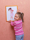 Smiling girl hanging up a self portrait Royalty Free Stock Photo