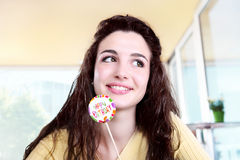 Smiling girl, happy birthday greetings concept, with lollipop. Sitting in bar stock photography