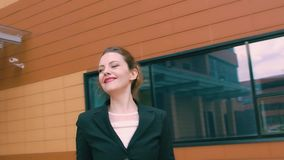 Smiling girl is happy and incendiary dances. beautiful woman on the background of the business building. SLOW MOTION. Two businessmen are having fun and laughing stock footage