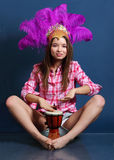 Smiling girl in hat with feathers sits on floor and beats drum Royalty Free Stock Photo