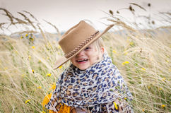 Smiling girl with hat in head in autumn grass Stock Photography