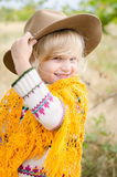 Smiling girl with hat and orange pelerine in autumn season Royalty Free Stock Image