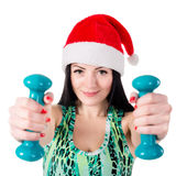 Smiling girl in hat of Santa Claus doing exercises with dumbbell Stock Images