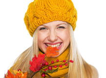 Smiling girl in hat and scarf biting autumn leaf Royalty Free Stock Photos