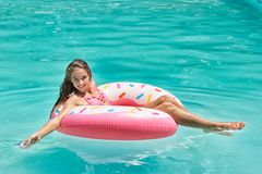 Smiling girl have fun floating on inflatable donut in blue swimming pool royalty free stock image