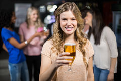 Smiling girl having a beer with her friends royalty free stock images