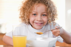 Smiling girl having breakfast in the kitchen Royalty Free Stock Image