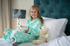 Smiling girl having breakfast with teady bear on bed Royalty Free Stock Images