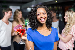 Smiling girl having a cocktail with her friends royalty free stock images