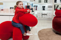 Smiling girl having fun in a big red toy Stock Images
