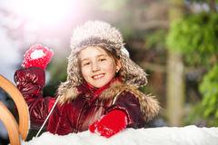 Smiling girl having fun with snowball fight. At the sunny winter day royalty free stock image