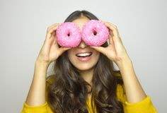 Smiling girl having fun with sweets isolated on gray background. Attractive young woman with long hair posing with doughnuts Royalty Free Stock Photo