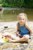 Smiling  girl having picknick on the riverside Royalty Free Stock Photo