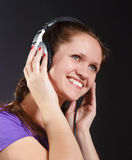 Smiling girl in the headphones. On a black background Stock Photography