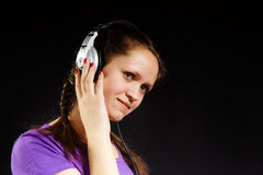 Smiling girl in the headphones. On a black background Stock Photos