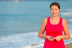 Smiling girl in headphones. On the background of the sea Stock Photos