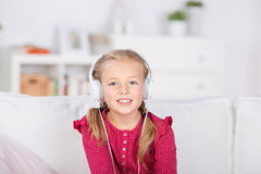 Smiling girl with headphones. Blond smiling girl with headphones at home Royalty Free Stock Photos
