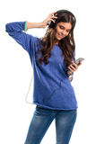 Smiling girl in headphones. Lady holds a cell phone. Casual clothes and electronic gadget. Check out the sound quality Stock Photo