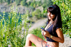 Smiling girl with headphones listening to music on the mountain. Tanned smiling girl with headphones listening to music on the mountain lake at sunny summer day Royalty Free Stock Image