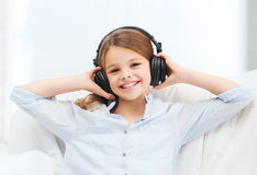Smiling girl with headphones listening to music. People, children and technology concept - smiling girl with headphones listening to music at home Stock Photos