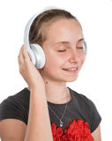 Smiling girl in headphones. Listening to music on a white background Stock Photos