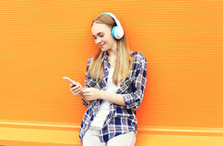 Smiling girl in headphones listens to music and using smartphone. Over orange background Stock Photography