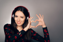 Smiling Girl with Headphones Making Heart Sign Royalty Free Stock Photo