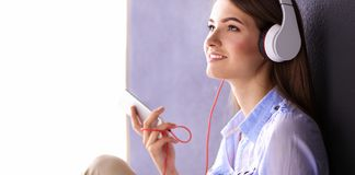 Smiling girl with headphones sitting on the floor near wall. Smiling girl with headphones sitting on the floor Royalty Free Stock Image