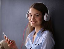 Smiling girl with headphones sitting on the floor Stock Photo
