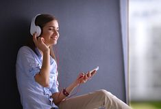 Smiling girl with headphones sitting on the floor Royalty Free Stock Photography