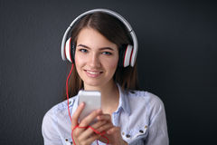 Smiling girl with headphones sitting on the floor Royalty Free Stock Image