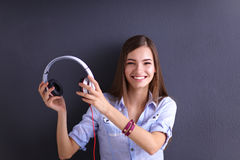 Smiling girl with headphones sitting on the floor Stock Photos